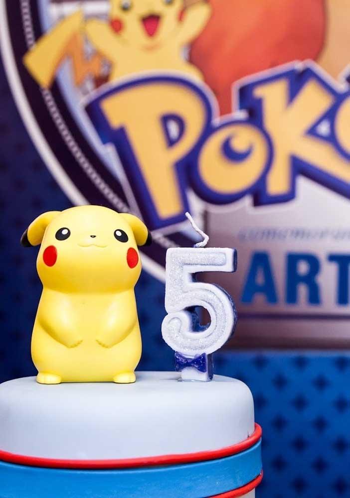 No topo do bolo pokemon nada melhor do que colocar o personagem Pikachu ao lado da vela.