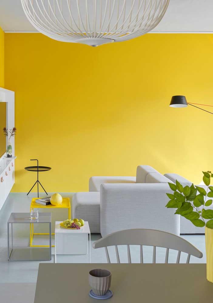Sala amarela e branca com detalhes em cinza. A iluminação natural traz ainda mais aconchego para decor