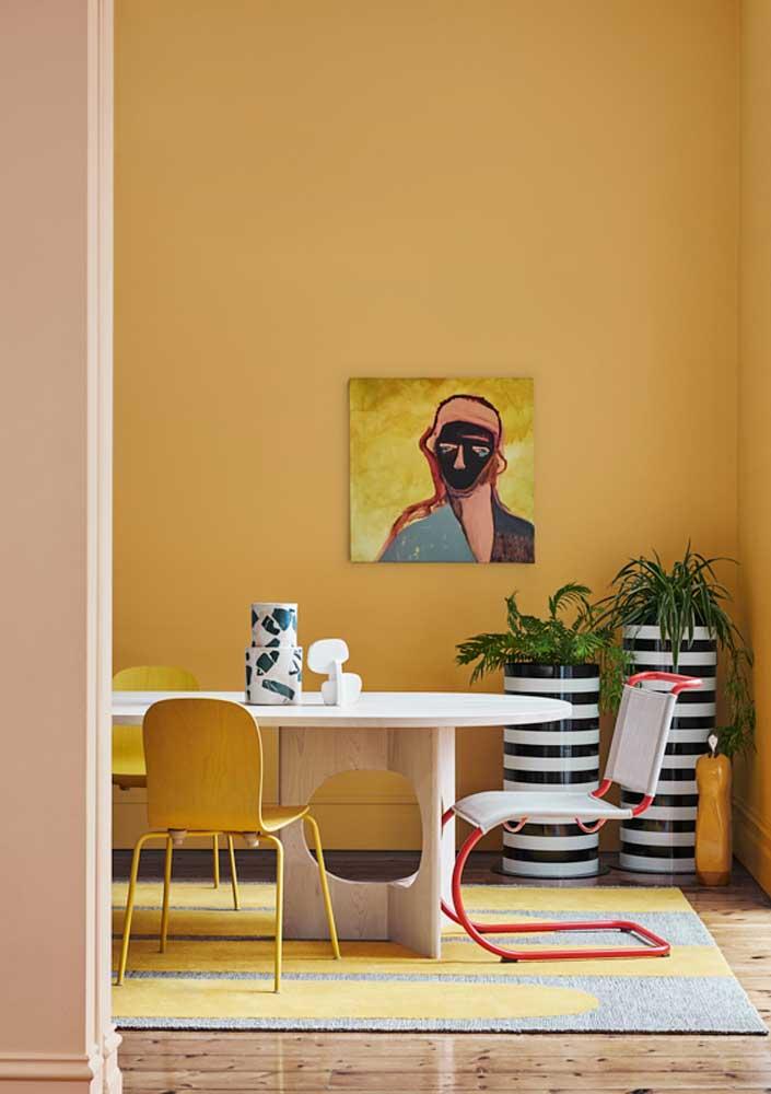 Quente e cheia de energia, essa sala impressiona pelo uso dramático do amarelo que recobre toda a parede e ainda colore o tapete e as cadeiras