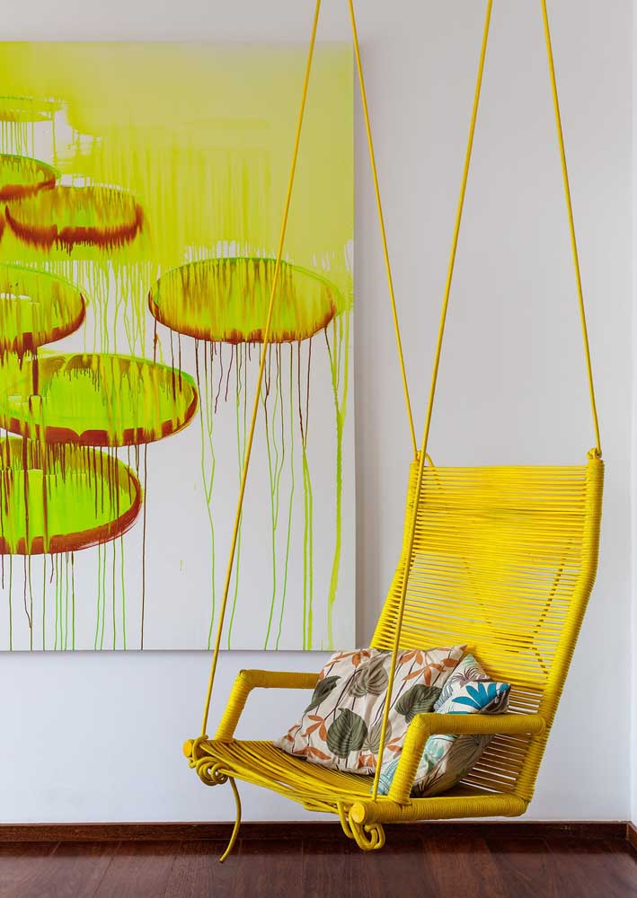 Já nessa sala de estar contemporânea, o amarelo se faz presente em elementos de grande apelo visual, como a poltrona suspensa e o quadro