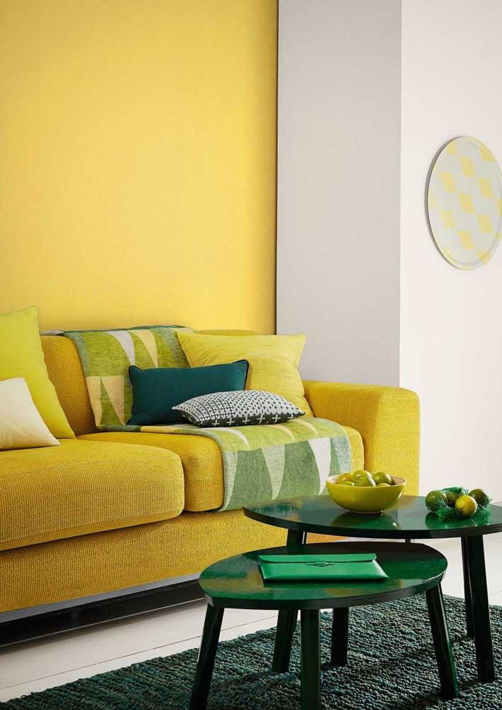 Parede e sofá amarelos para criar um conjunto visual. Os tons de verde garantem frescor para a sala