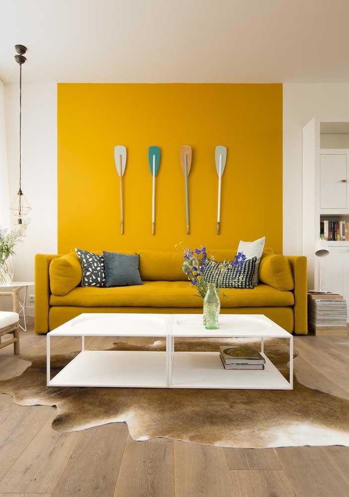Nessa sala, apenas a faixa de parede atrás do sofá recebeu pintura amarela
