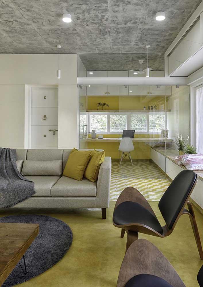 Que tal uma sala de estar com piso amarelo? Note que aqui, a cor está presente apenas no chão, colorindo o tapete e o piso que leva até a cozinha