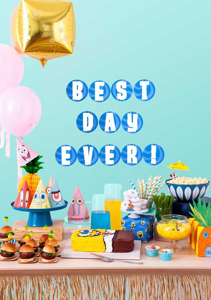 Mesa do bolo para uma festa Bob Esponja simples. Repare no formato quadrado do bolo e nos chapéus de aniversário com os personagens