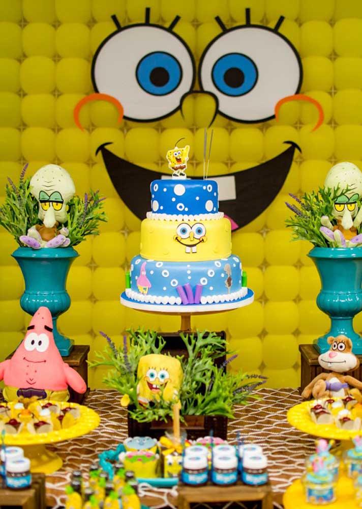 Mesa decorada com bolo Bob Esponja. Logo atrás, um descontraído painel de balões dá forma ao personagem principal