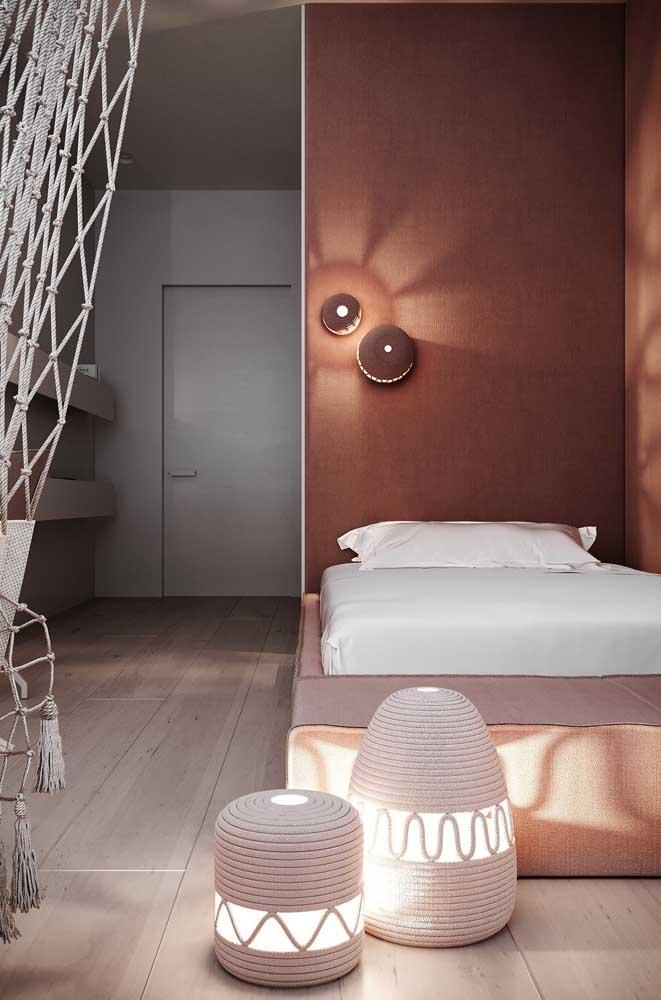 Iluminação indireta e tons terrosos dão o clima aconchegante para esse quarto pequeno de solteiro