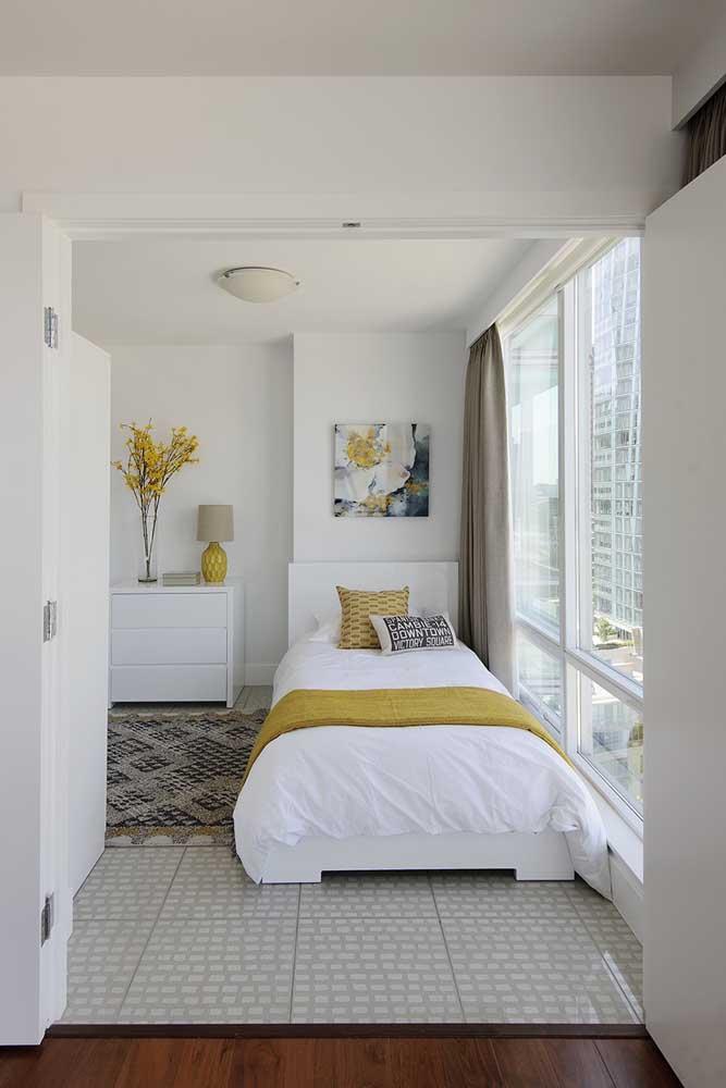 Um típico quarto de solteiro pequeno decorado com tons claros. A pedida certa para quem não quer errar
