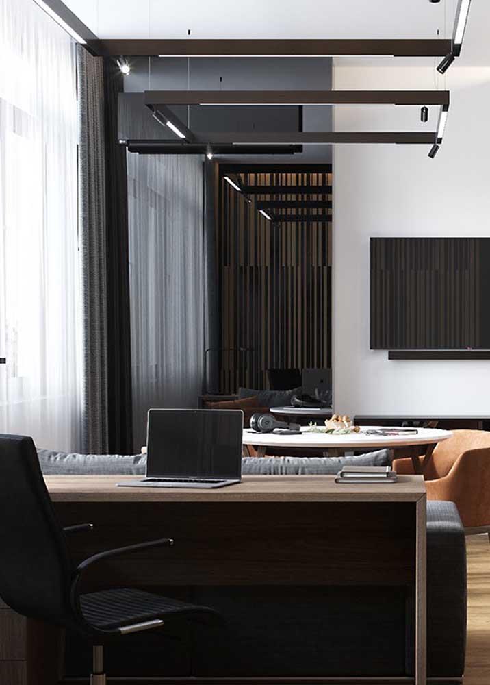 Nesse modelo de escritório em casa, a mesa de trabalho foi encaixada atrás do sofá da sala