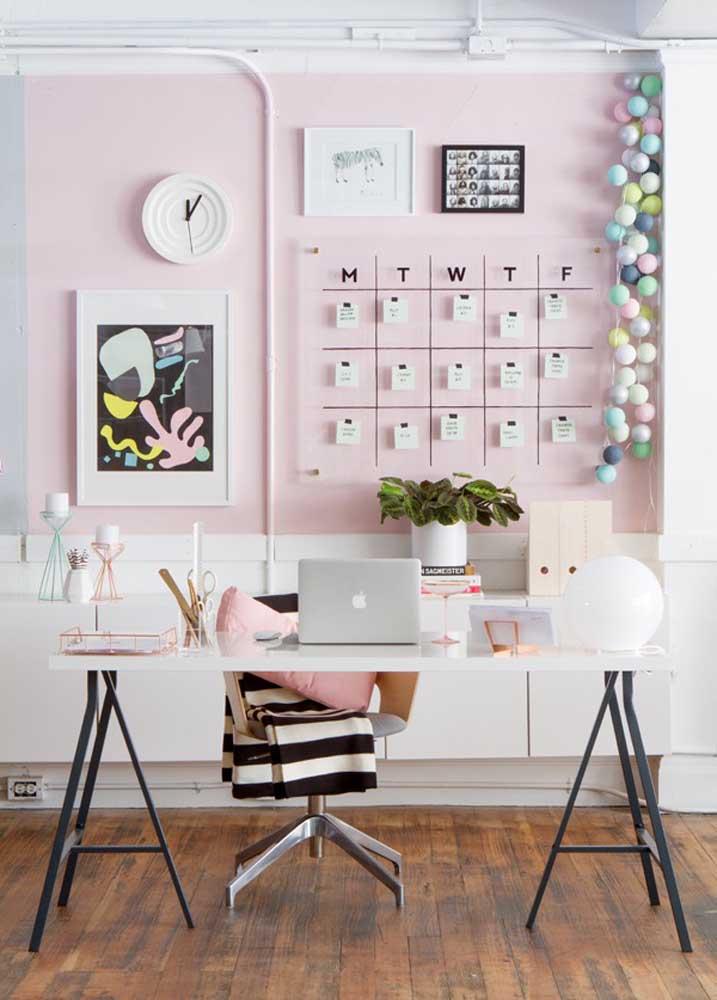Escritório em casa moderno com mesa de cavalete e parede cor de rosa
