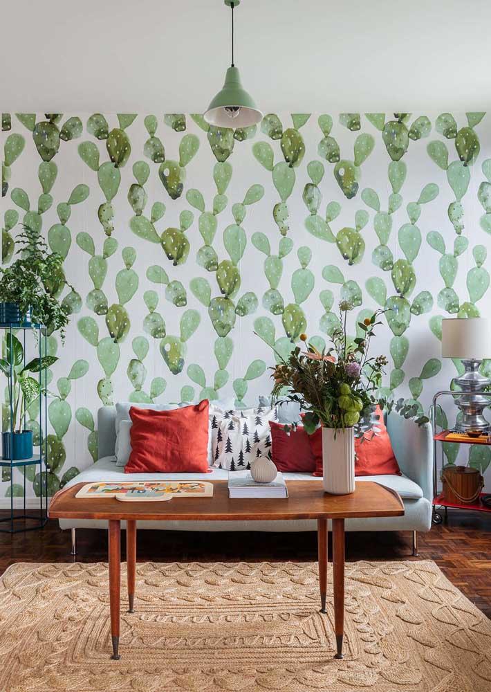 O verde dessa sala fica por conta do papel de parede de folhas e as plantas
