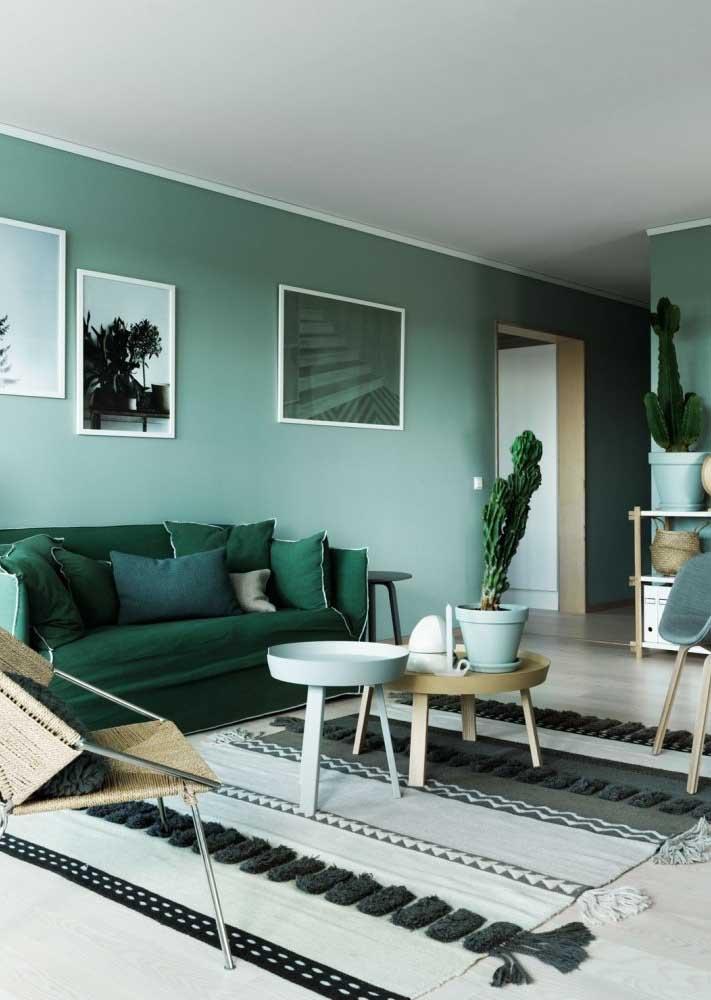 Sala com parede verde combinada com sofá em um tom mais escuro
