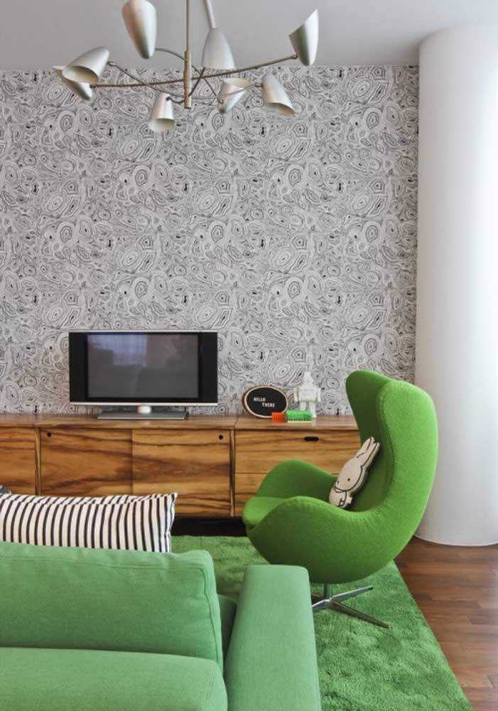 O que acha de combinar o sofá verde com o tapete verde? Aos fundos, um papel de parede cinza estampado