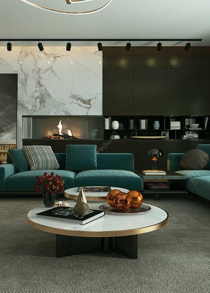 Sala com sofá verde. Para combinar, tapete cinza e parede preta com revestimento de mármore