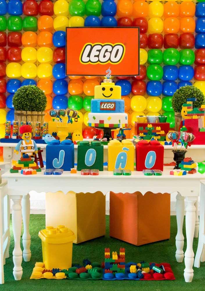 Mesa do bolo decorada com tema Lego. Repare que o painel aos fundos foi feito com balões imitando as pecinhas do brinquedo