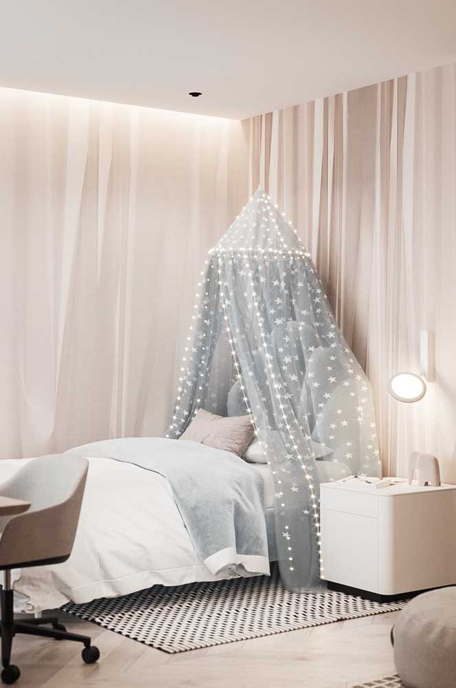 Romântico e delicado, esse quarto de solteiro feminino surpreende pelo uso do tule e das luzes de pisca pisca sobre a cama