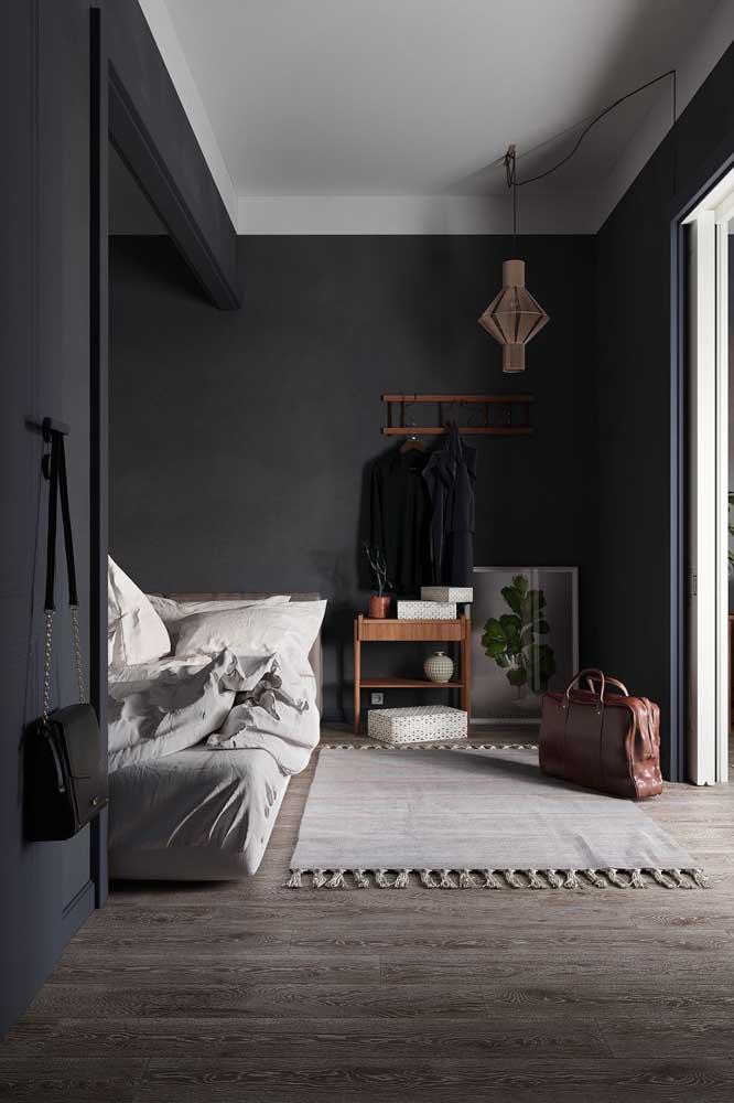 Já aqui, o quarto de solteiro feminino grande e cheio de luz natural apostou em paredes pretas para se diferenciar