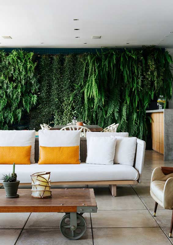 Essa varanda grande trouxe um conjunto de sofá de fibra sintética para compor o espaço