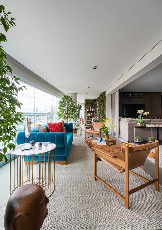 Aqui, a varanda coberta pode se dar ao luxo de ter um sofá de veludo azul