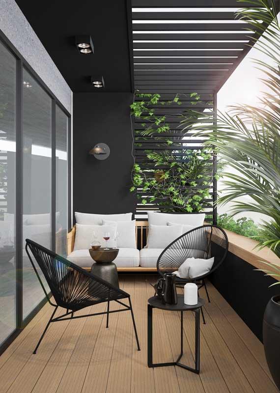 Aqui, a opção foi usar um sofá de tom claro para contrastar com a varanda de paredes pretas