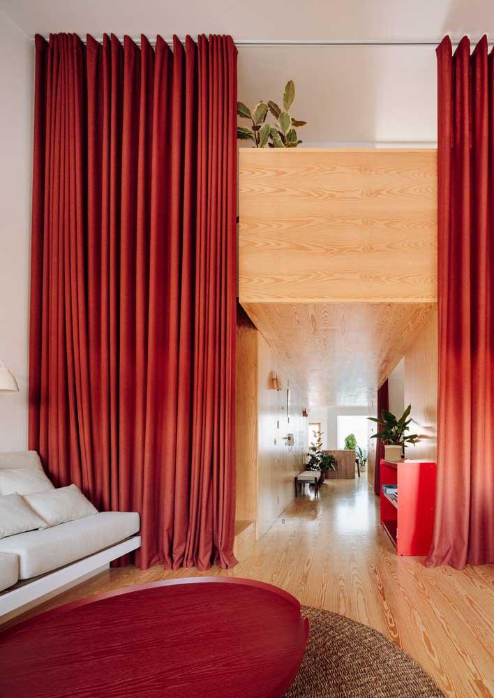 Sala com cortina vermelha que funciona também como divisória de ambientes