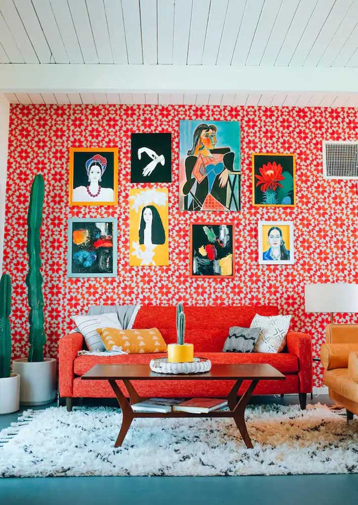 Sala com parede vermelha super descontraída. Os quadros deixam a decoração ainda mais completa