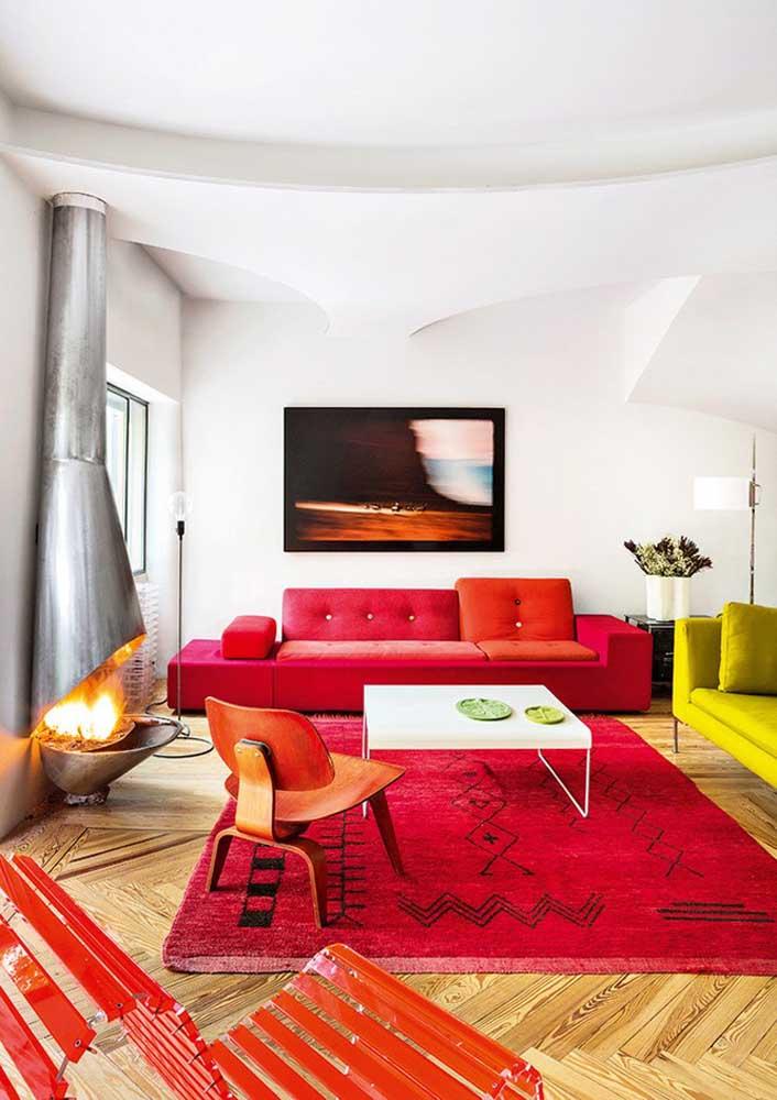 Sofá, tapete e poltronas vermelhas se destacam nessa sala de paredes brancas. O sofá amarelo limão faz o contraponto na decoração