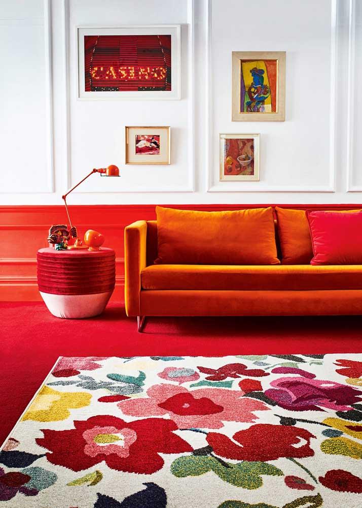 Uma sala clássica decorada com piso e meia parede vermelha. O vermelho ainda aparece de modo pontual no tapete, no sofá, na luminária e nos quadros