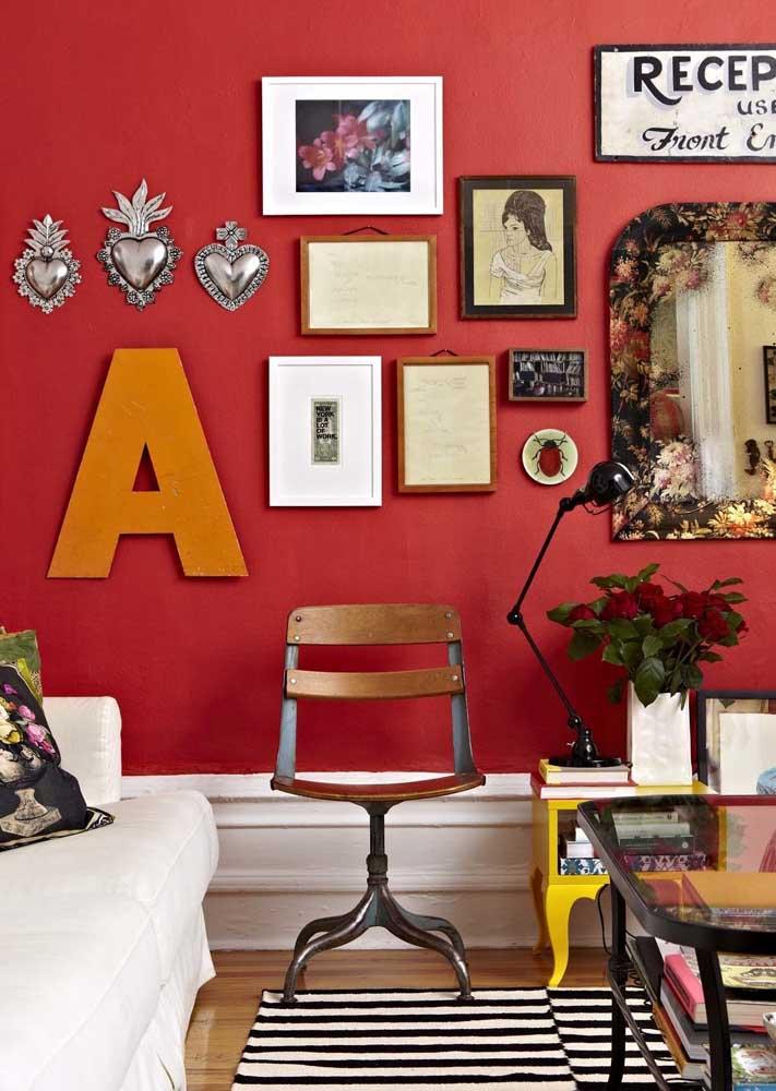Sala com parede vermelha, super contemporânea, decorada com quadros