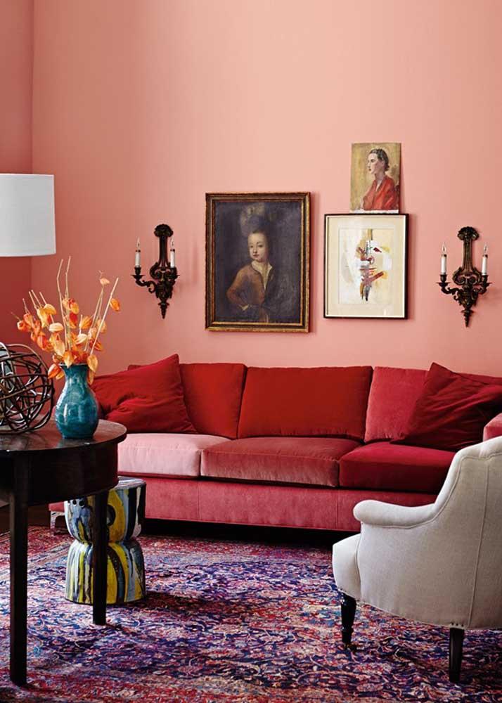 Sala com sofá vermelho e de veludo. Quer mais? Então pinte a parede de rosa!