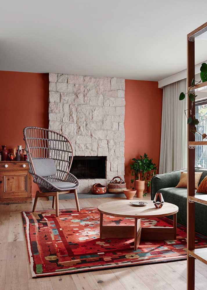 Sala vermelha rústica. A sensação de conforto fica ainda mais acentuada com a presença de elementos em madeira e pedra