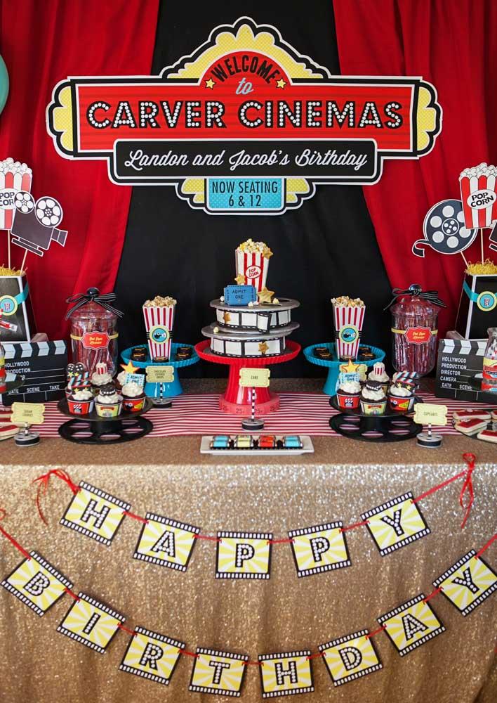 Festa cinema decorada em tons de preto, vermelho e amarelo. Na mesa do bolo, saquinhos de pipoca e cupcakes