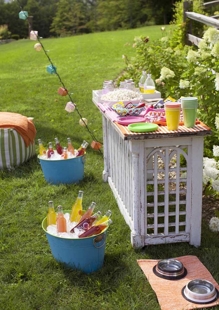 A festa cinema ao ar livre ainda traz uma mesa de aperitivos e bebidas, como se fosse um piquenique