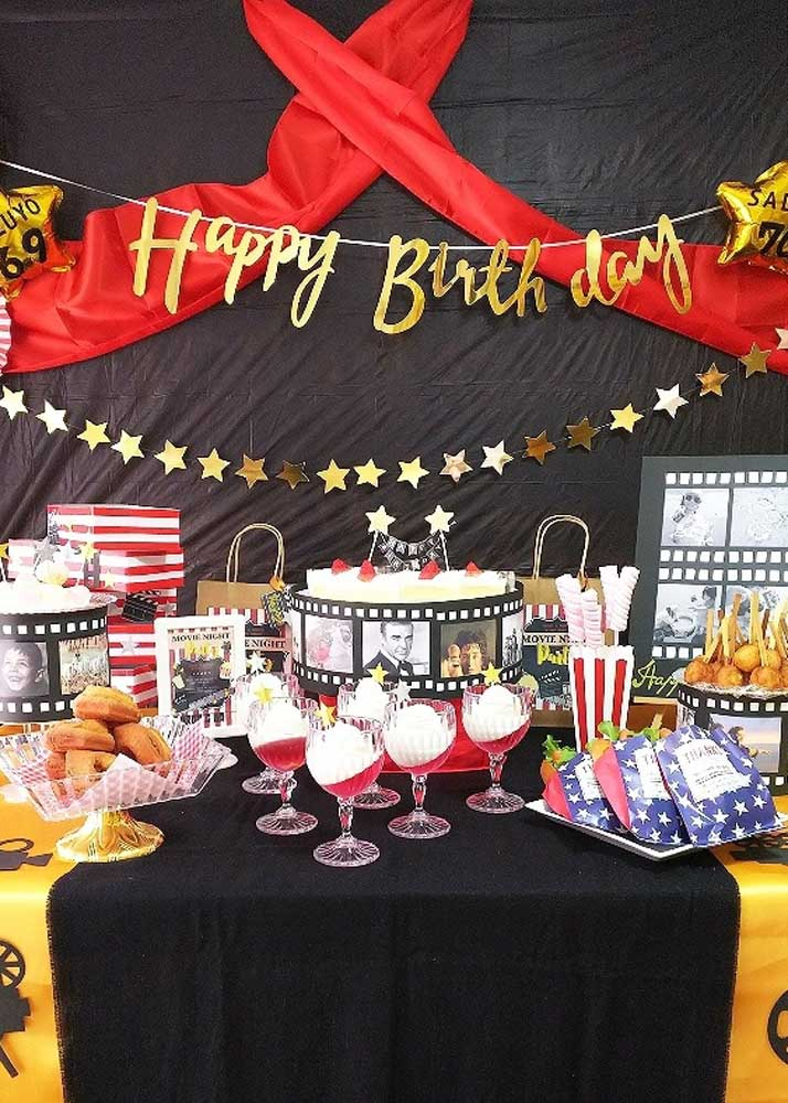Festa cinema com painel preto e estrelas douradas. O tecido vermelho traz a tona o clima hollywoodiano