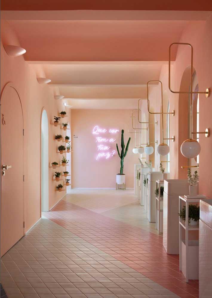 O longo corredor rosa traz um letreiro luminoso de neon bem aos fundos
