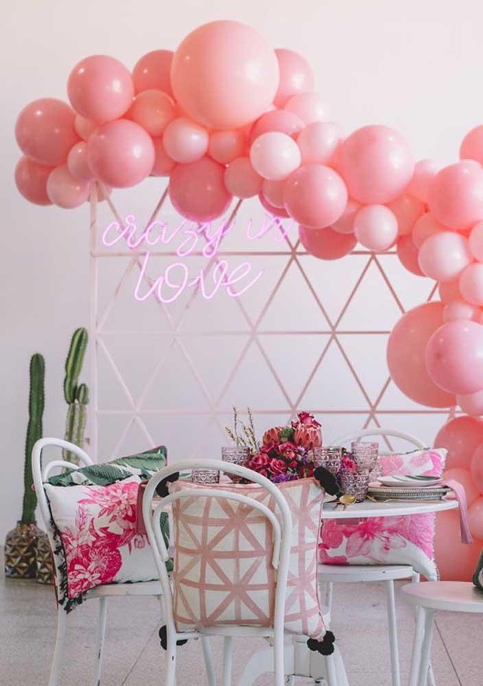 Letreiro neon rosa combinando com os balões da festa