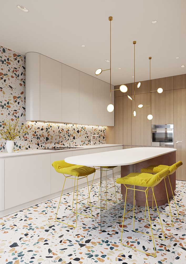 Cozinha moderna com piso e revestimento de granilite. A base clara garantiu o destaque dos grãos coloridos