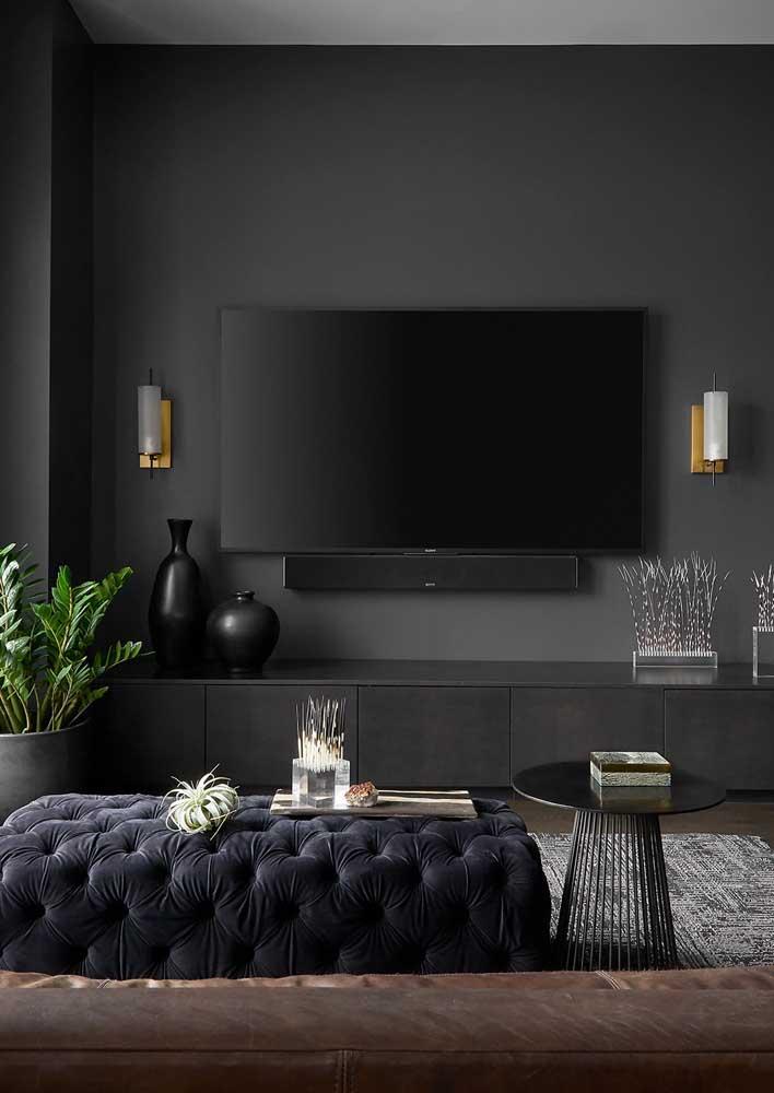 """Sala preta e cinza. Repare que a parede preta ajuda a """"camuflar"""" a TV e o rack"""