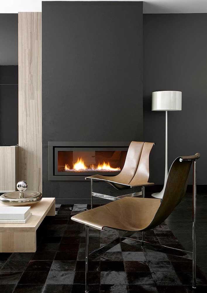 Sala preta com toque acolhedor da madeira e dos detalhes em couro