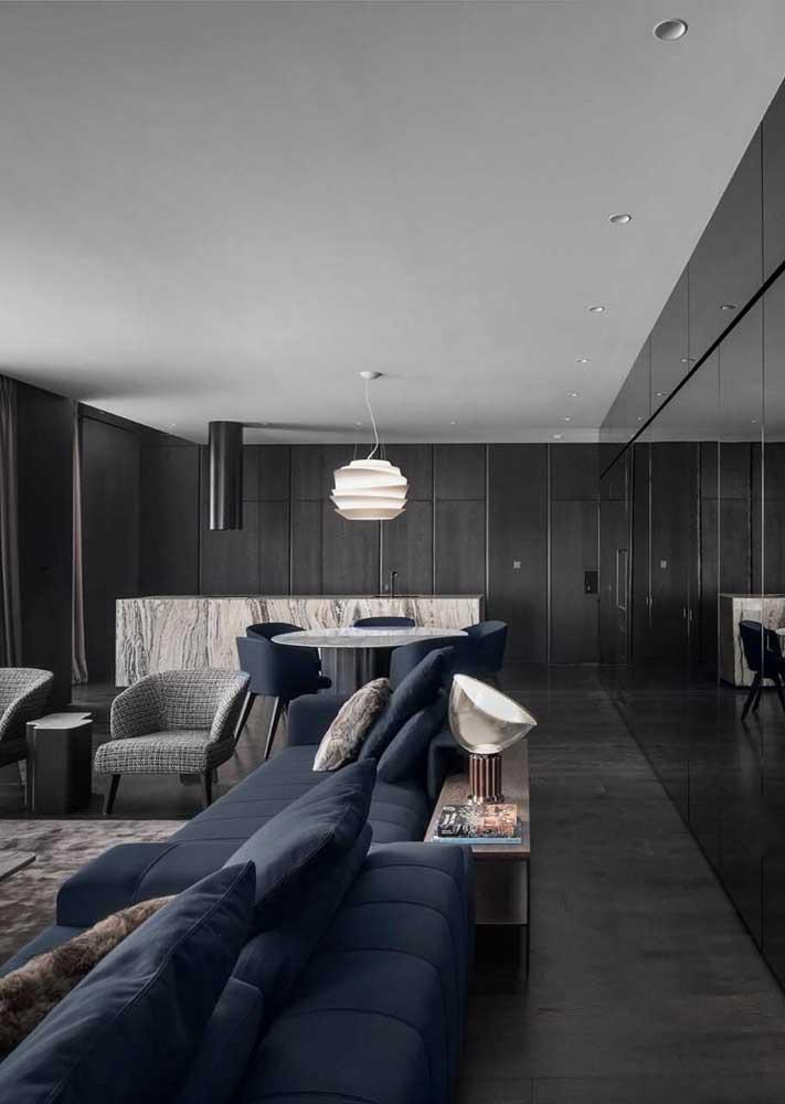 O ambiente integrado apostou no piso e nas paredes pretas. O sofá azul quebra a monotonia de tons