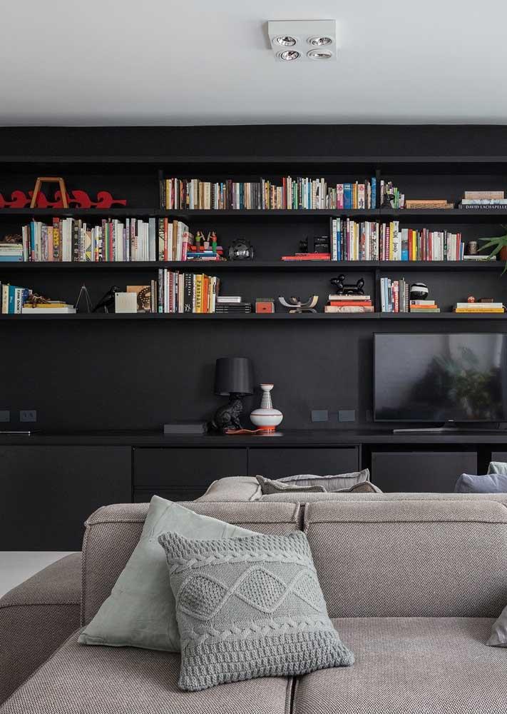 Sala com parede e prateleiras pretas. A cor traz integração para o conjunto