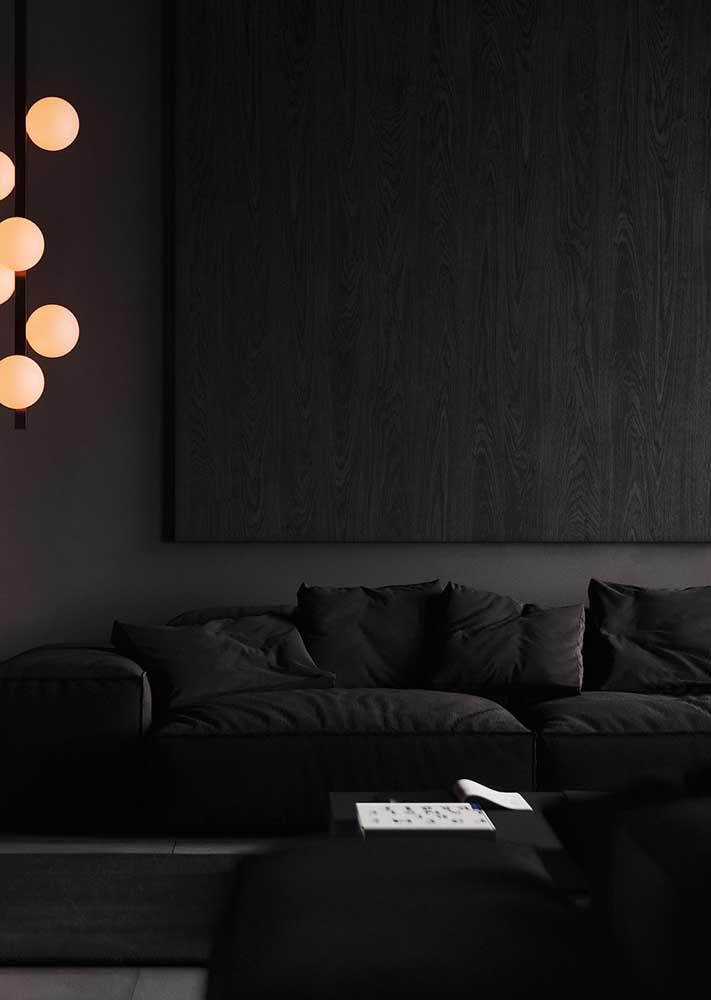 Aqui, a sala preta ganha conforto extra com o uso das luzes amarelas