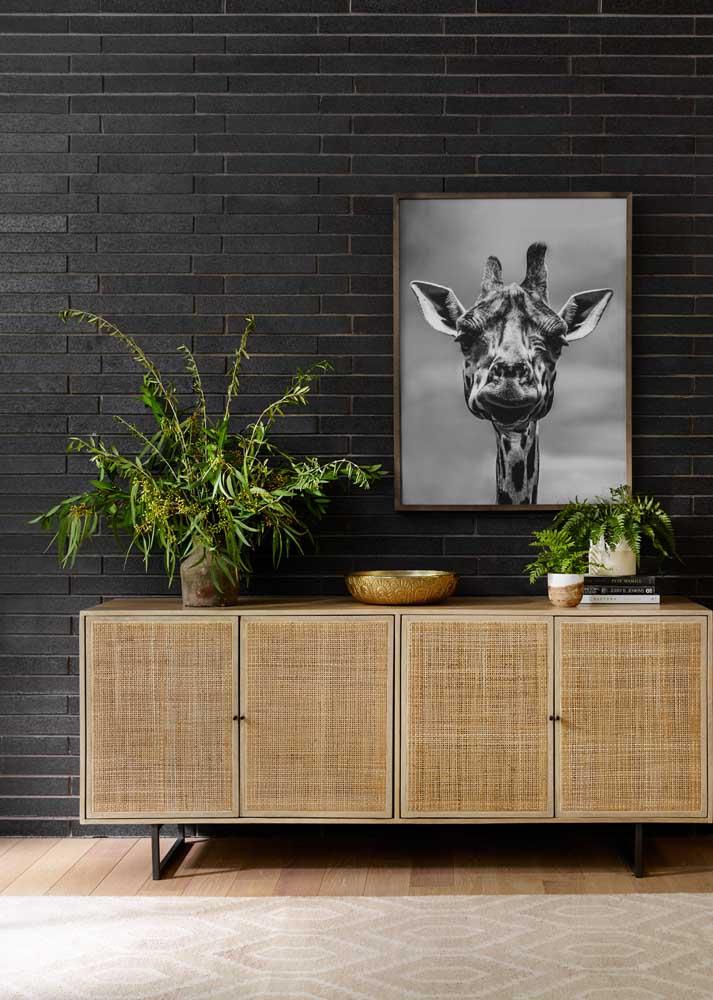Sala com parede preta valorizada pelas texturas do móvel e das plantas