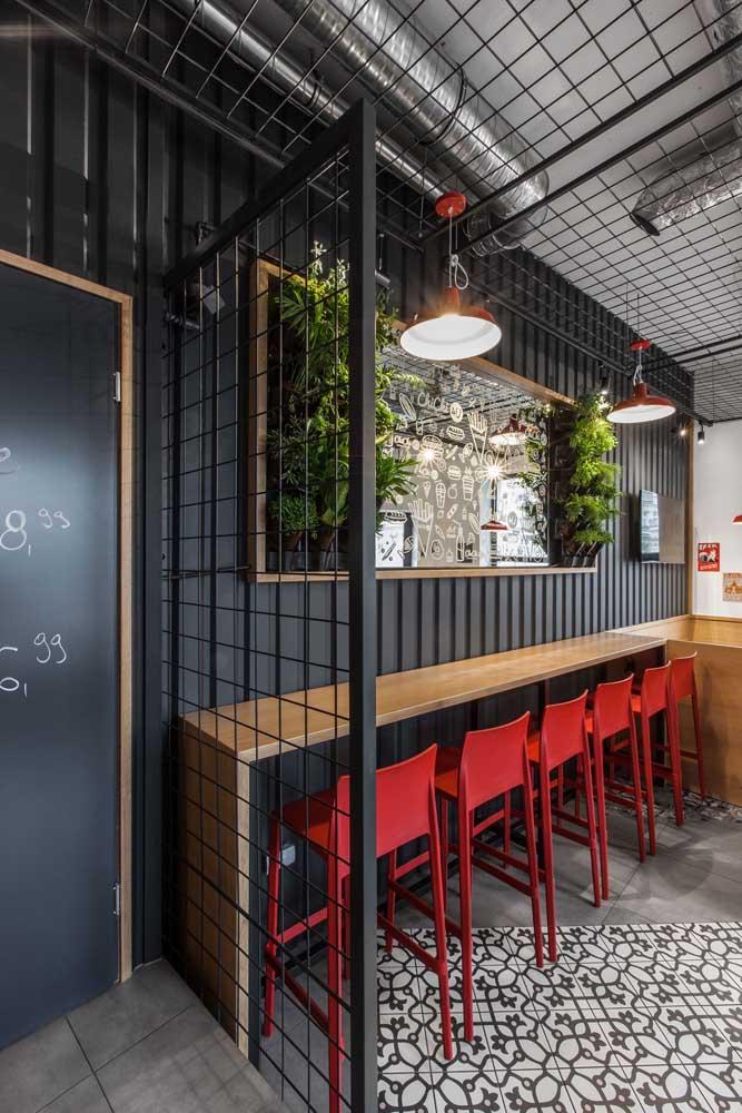 Bar com revestimento de telha sanduíche nas paredes. Além de ajudar no aquecimento do ambiente, a telha se encaixa com o estilo decorativo do local