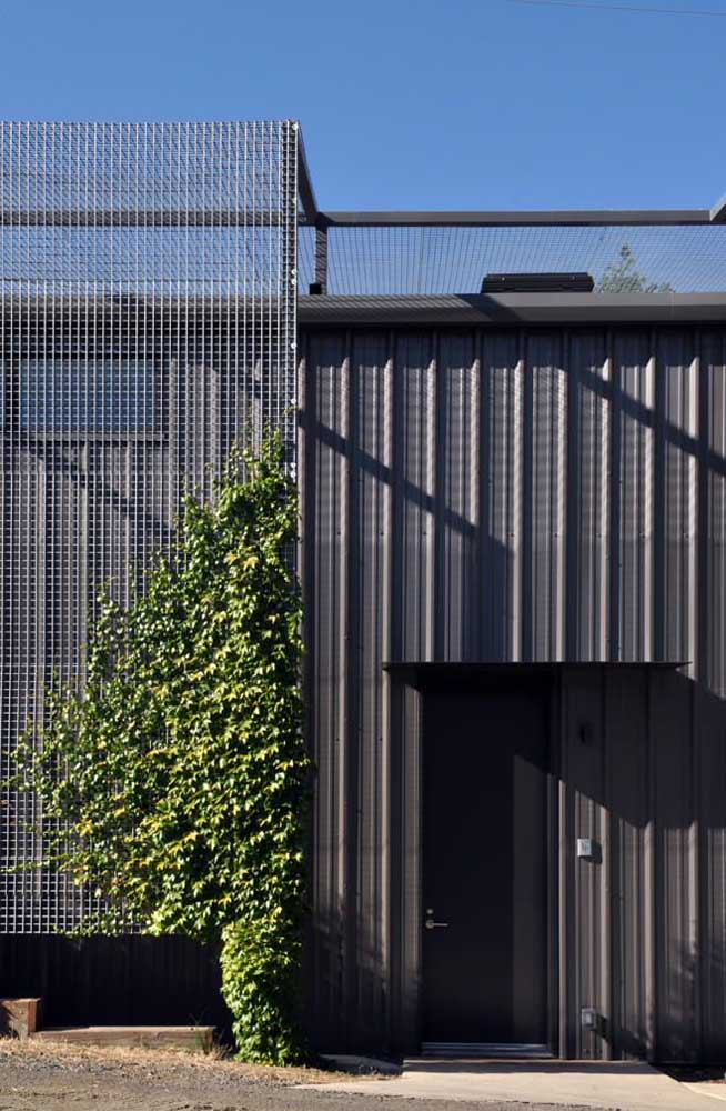 Fachada de casa moderna e estilosa revestida com telha sanduíche preta e telas aramadas