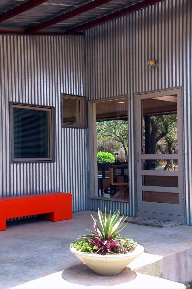 Já nesse hall de entrada, as telhas sanduíches em tom metálico ficaram incríveis com o contraste do sofá vermelho