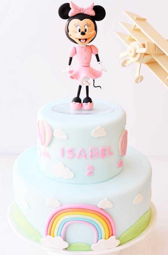 Bolo da Minnie com tema de arco-íris. A personagem marca presença no topo do bolo