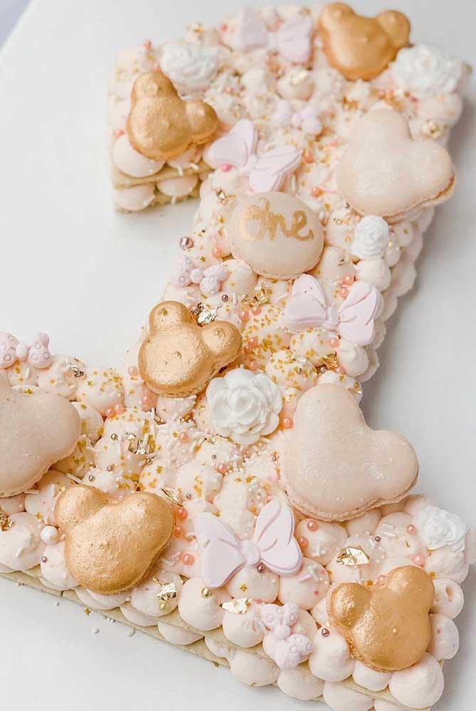 Bolo da Minnie para festa de um ano. Para a decoração, biscoitinhos no formato da personagem, além de flores e laços