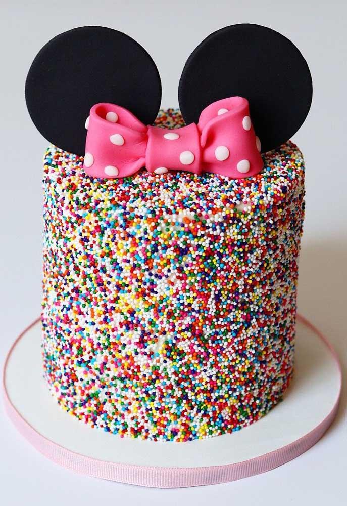 Bolo da Minnie decorado com confeitos coloridos. Para caracterizar o tema, orelhinhas e laço no topo