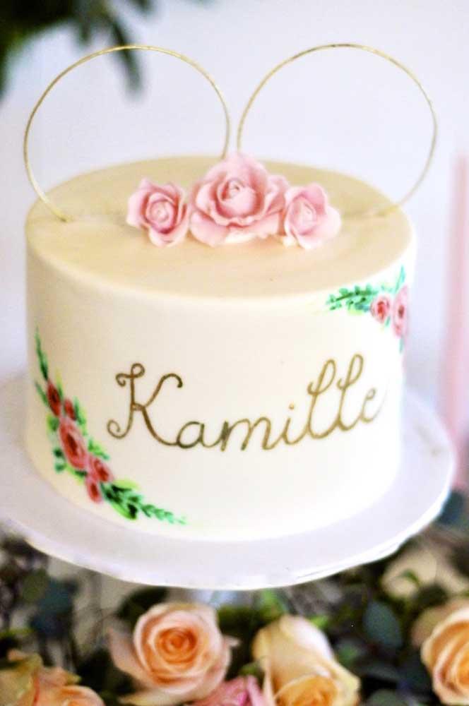 Esse bolo entra no tema da Minnie graças as orelhinhas douradas no topo