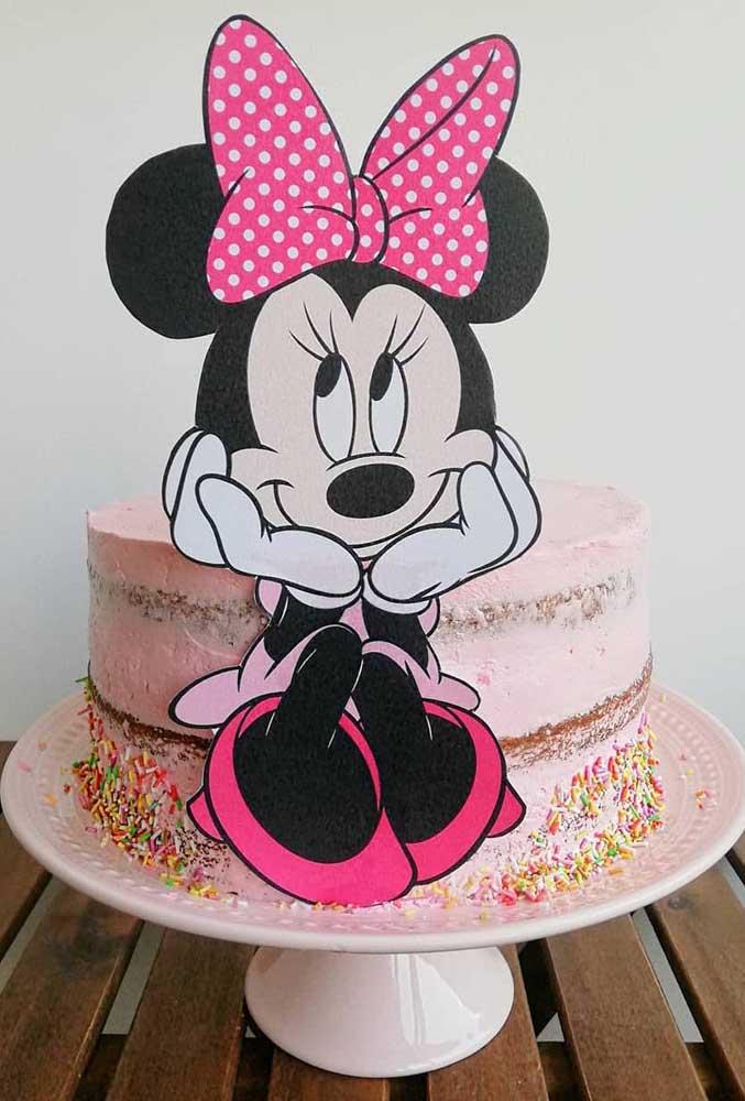 Bolo da Minnie redondo e espatulado. Para decoração, um totem e confeitos coloridos